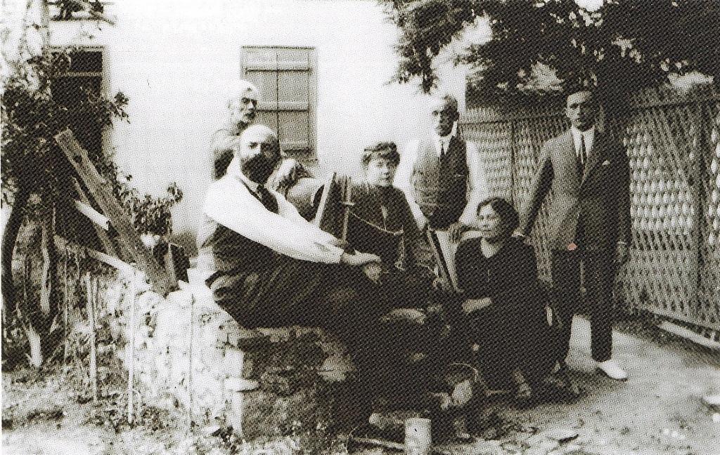 Νικόλαος Χειμώνας (όρθιος αριστερά) και Όλγκα Χειμώνα (καθισμένη στο κέντρο) στην αυλή του σπιτιού τους στην Αθήνα, 1925